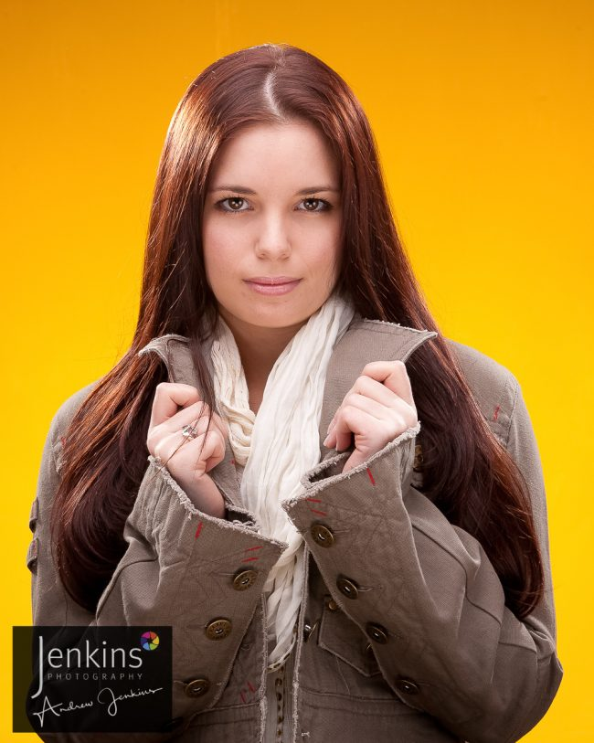 Studio photos Katie wearing brown jacket cream scarf yellow back ground